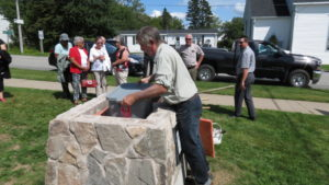 Placing the container with the time capsule materials in the cairn